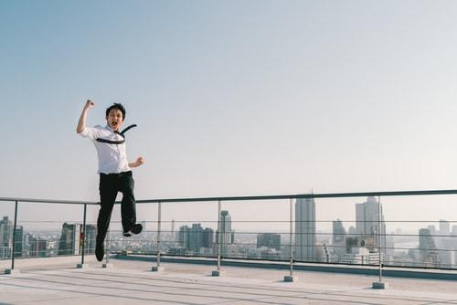 屋上でガッツポーズしている男性